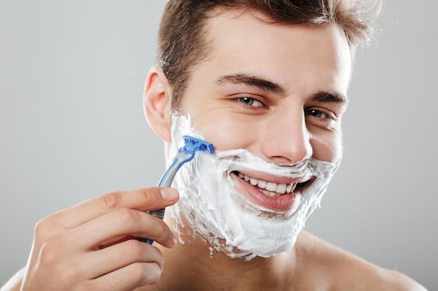 Mec brunette masculin aux cheveux courts noirs se raser le visage avec un rasoir et du gel ou de la crème étant satisfait sur un mur gris