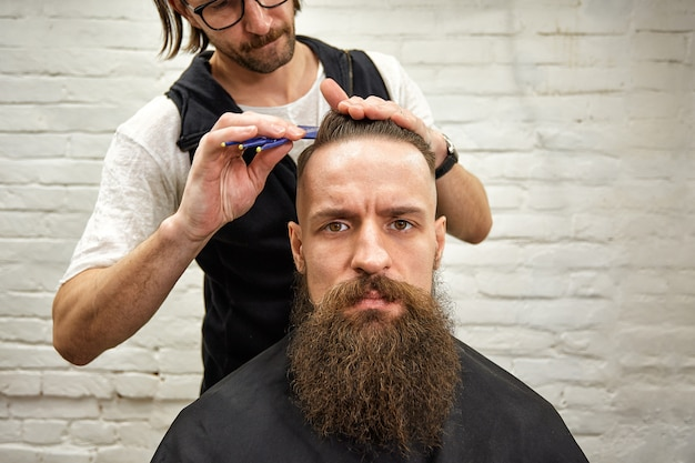 Mec brutal dans un salon de coiffure moderne. le coiffeur fait de la coiffure un homme avec une longue barbe. le coiffeur principal fait la coiffure avec des ciseaux et un peigne