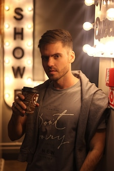 Un mec avec un café à la main regarde la caméra