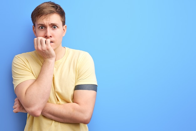 Un mec caucasien a l'air stressé et nerveux avec les mains sur la bouche qui se rongent les ongles. problème d'anxiété. fond bleu isolé