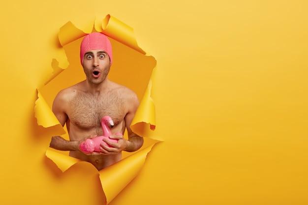 Un mec caucasien choqué se tient à travers un trou de papier, a le torse nu