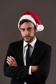Mec caucasien en pull rouge et chapeaux de père noël