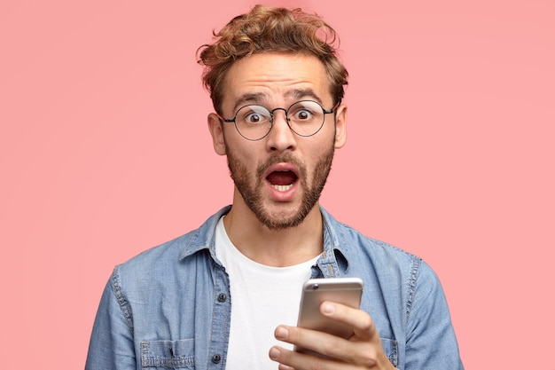 Un mec caucasien stupéfait avec une expression surprise, tient le cellulaire dans les mains, reçoit une notification inattendue