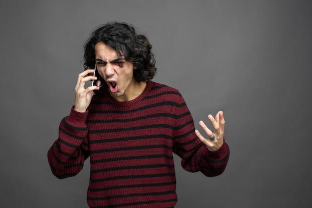 Mec en colère parle avec téléphone