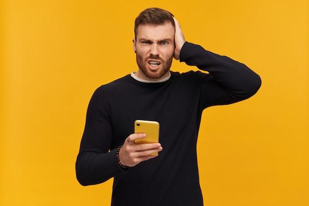 Mec confus et incertain aux cheveux bruns et à la barbe. a un piercing. porter un pull noir. se gratte la tête et tient le smartphone. regarder perplexe, isolé sur mur jaune