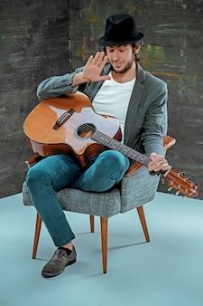Mec cool assis avec guitare sur gris
