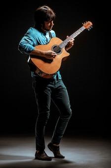 Mec cool avec chapeau debout avec guitare sur fond sombre de studio