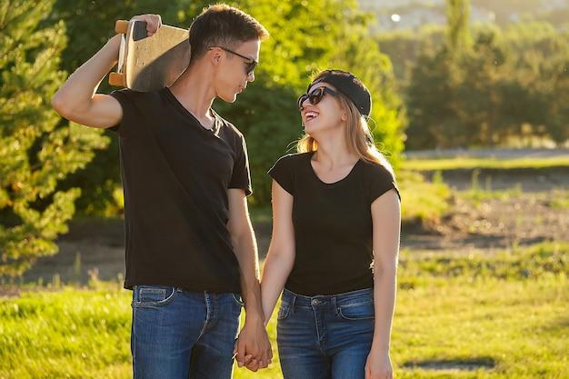 Un mec cool et une jolie fille en lunettes de soleil, un jean et un t-shirt noir faisant de la planche à roulettes se tenant la main dans le parc d'été.