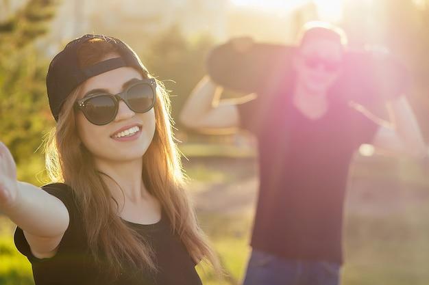 Un mec cool et une jolie fille en lunettes de soleil, un jean et un t-shirt noir faisant de la planche à roulettes se tenant la main photographié prennent des photos en selfie au téléphone dans le parc d'été