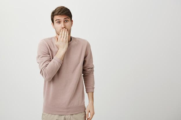 Un mec coupable mignon dit oups, couvrez la bouche avec un air embarrassé