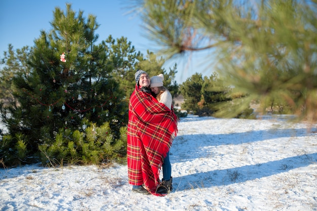 Mec dans la couverture à carreaux rouge enveloppe la fille pour qu'elle se réchauffe