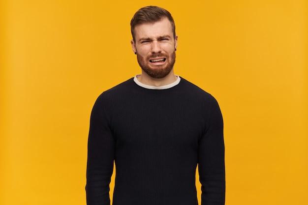 Mec déprimé barbu, homme malheureux aux cheveux brune. a un piercing. porter un pull noir. visage pleurant et ironique plein de larmes. isolé sur mur jaune