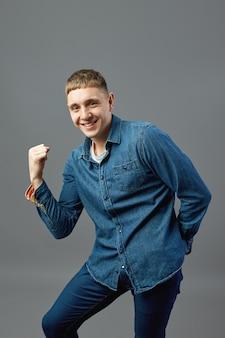 Un mec drôle vêtu d'une chemise en jean montre son pouvoir avec sa main en studio sur fond gris.
