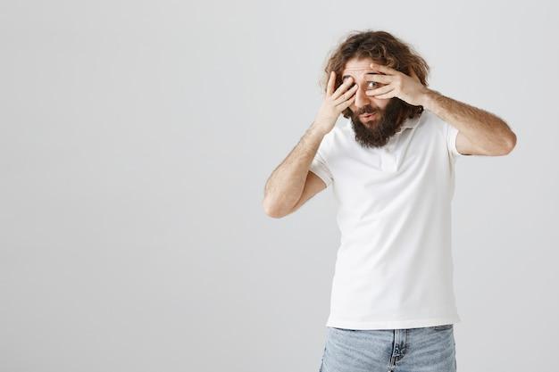 Un mec du moyen-orient excité jetant un coup d'œil à travers les doigts, l'air intrigué