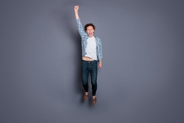 Mec élégant dans une chemise à carreaux bleue posant contre le mur gris