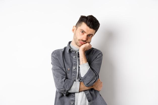 Un mec élégant ennuyé et réticent regarde la caméra sans émotions, assiste à une réunion ennuyeuse, debout sur fond blanc.