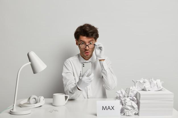 Un mec embarrassé regarde avec émerveillement le smartphone, porte des lunettes transparentes