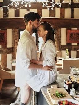 Mec embrasse la fille qui est assise sur la table de la cuisine, le concept de romance,