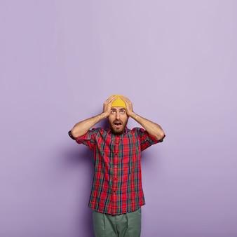 Un mec émotif surpris garde les deux mains sur la tête, porte un chapeau jaune et une chemise à carreaux, a expié le regard vers le haut