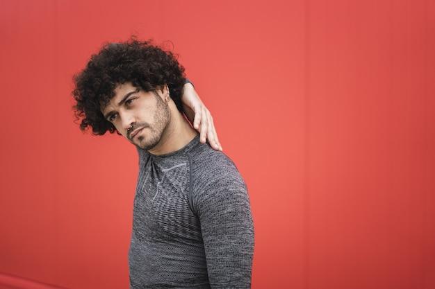 Mec espagnol attirant posant par le mur rouge avec une main derrière le cou