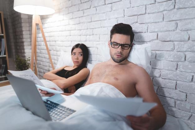 Un mec est allongé dans son lit et travaille sur un ordinateur portable.