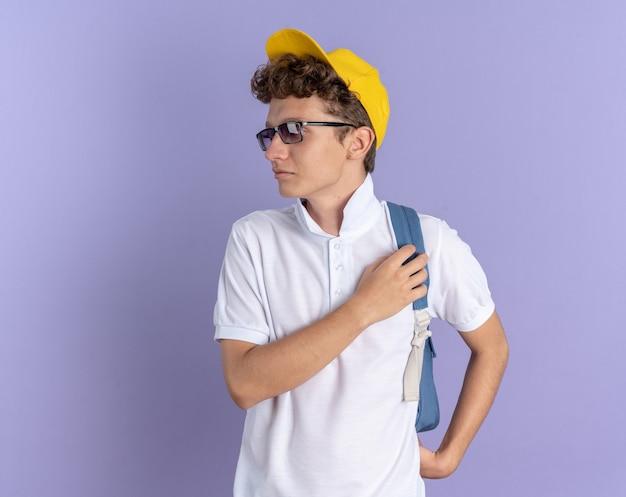 Mec étudiant en polo blanc et casquette jaune portant des lunettes avec sac à dos regardant de côté avec un visage sérieux