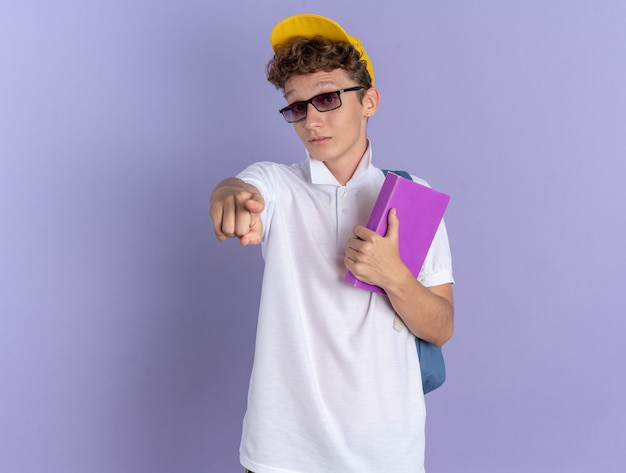 Mec étudiant en polo blanc et casquette jaune portant des lunettes avec sac à dos tenant un ordinateur portable pointant avec l'index à la caméra d'être surpris