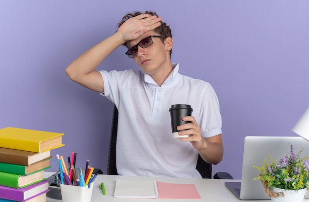 Mec étudiant en polo blanc portant des lunettes assis à la table avec des livres tenant une tasse de papier à la recherche de mal avec la main sur son front sur fond bleu
