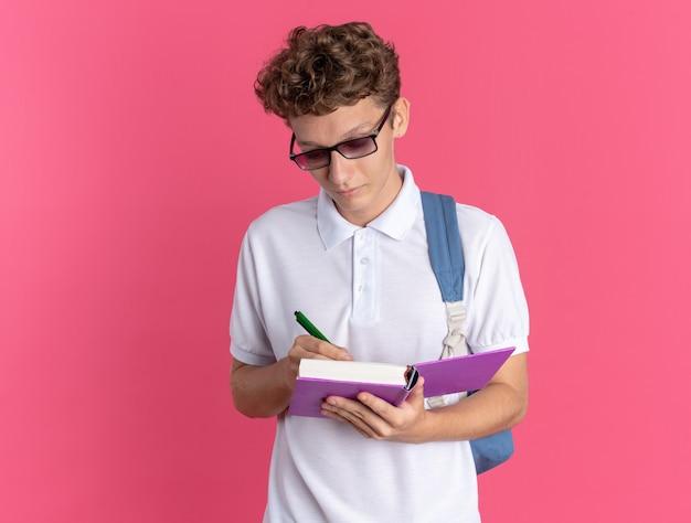 Mec étudiant en vêtements décontractés portant des lunettes avec sac à dos tenant un cahier et un stylo écrivant quelque chose avec un visage sérieux debout sur fond rose