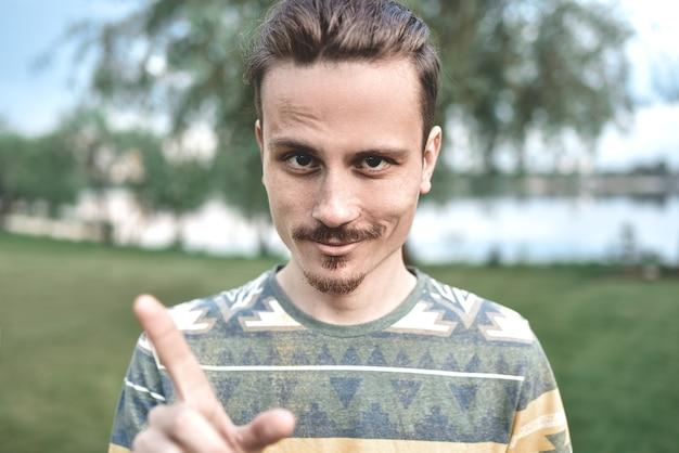 Un mec avec une expression sournoise sur son visage, montre un geste du doigt