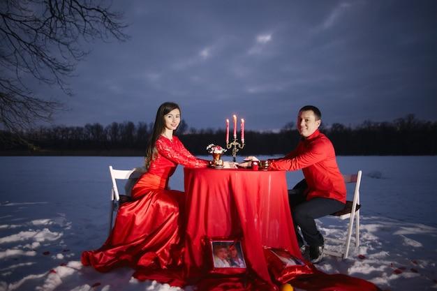 Un mec et une fille amoureuse s'asseoir dans des vêtements rouges à une table avec des bougies et s'accrocher à leurs mains sur un fond de neige