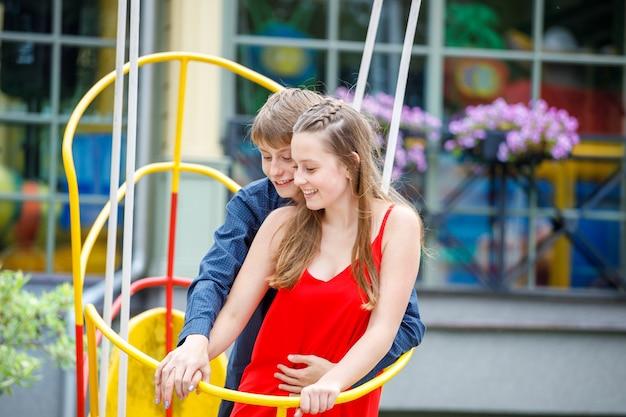 Mec avec une fille sur une balançoire dans le parc