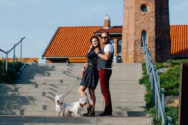 Mec avec une fille marchant autour de la ville avec deux chiens