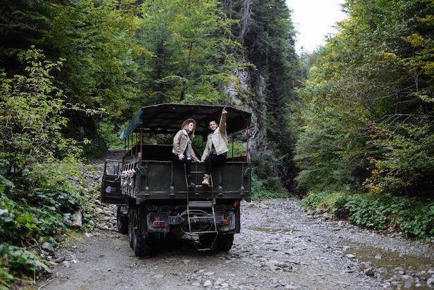 Mec et la fille sont assis sur la voiture dans les bois