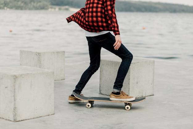 Mec en flanelle faisant de la planche à roulettes au bord du lac