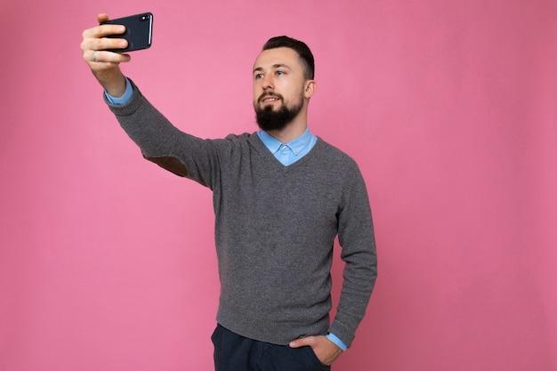 Mec sur fond rose prend un selfie