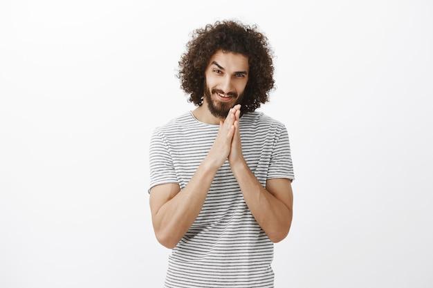 Un mec gourmand a un plan méchant. portrait d'homme aux cheveux bouclés intrigué avec barbe, frottant les paumes ensemble près de la poitrine et souriant