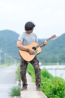 Mec avec guitare debout sur le barrage, pantalon cargo