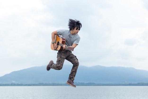 Mec avec guitare debout sur le barrage