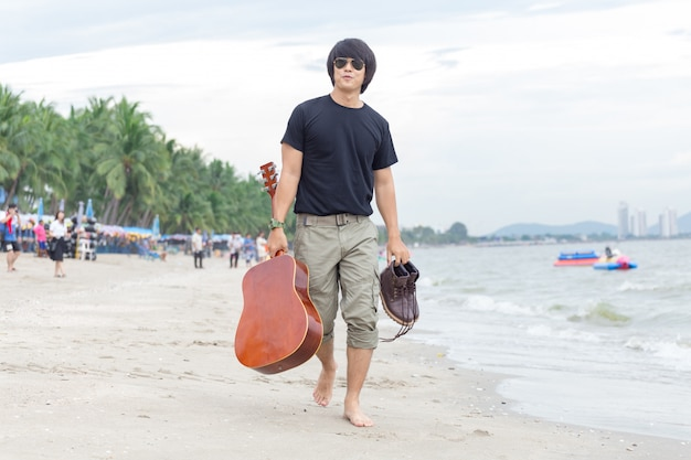 Mec avec guitare debout sur la plage, pantalon cargo