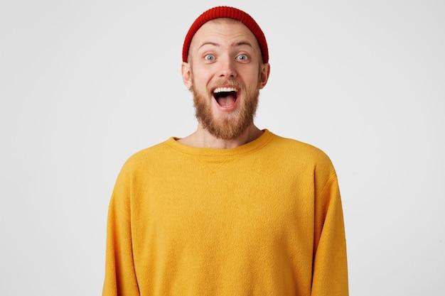 Un mec heureux est prêt à sauter du bonheur. homme barbu aux yeux bleus submergé d'émotions positives