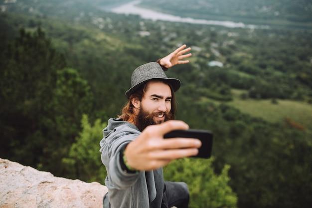 Un mec heureux en haute montagne à l'aide d'un téléphone portable prend un selfie.