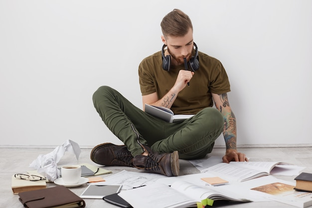Mec hipster concentré avec des tatouages, s'assoit les jambes croisées sur le sol, lit des livres et écrit des notes