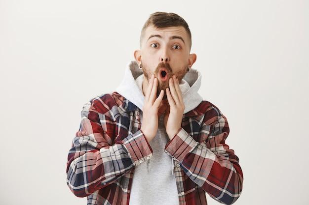 Un mec hipster étonné et impressionné laisse tomber la mâchoire et regarde étonné