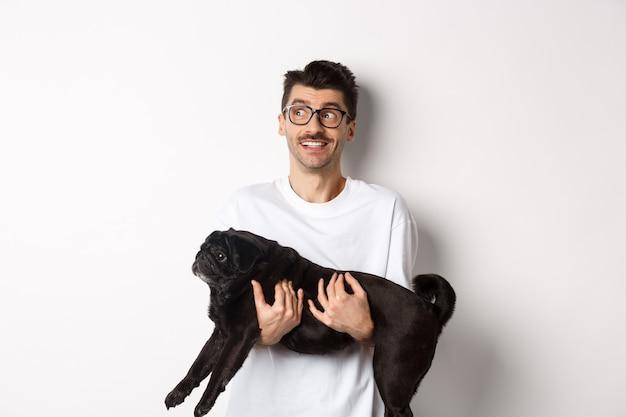 Mec hipster excité avec son chien regardant à gauche le logo. beau propriétaire de l'animal portant carlin noir et regardant la bannière promotionnelle, debout sur blanc.