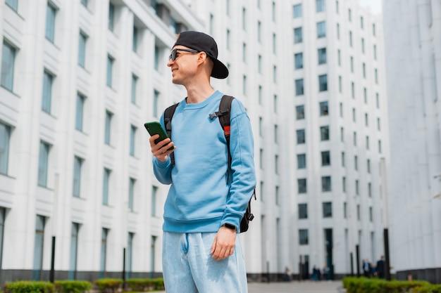 Mec hipster positif avec sac à dos debout en plein air tenant un smartphone tout en détournant les yeux avec le sourire