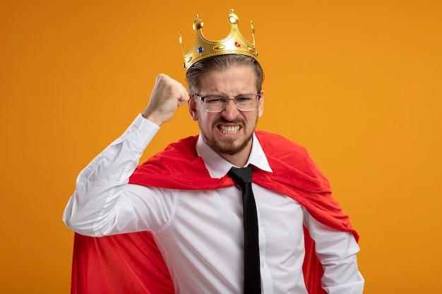 Mec jeune super-héros en colère portant une cravate et une couronne avec des lunettes levant le poing isolé sur orange