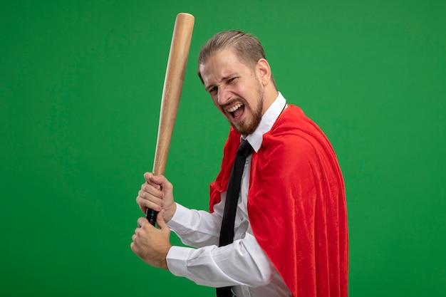 Mec jeune super-héros en colère tenant une batte de baseball isolé sur vert