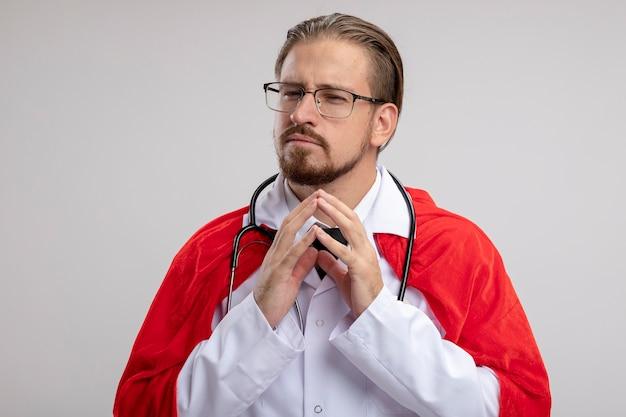 Mec jeune super-héros suspect portant une robe médicale avec stéthoscope et lunettes tenant par la main ensemble isolé sur fond blanc