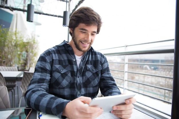 Mec joyeux utilisant gadget pour discuter